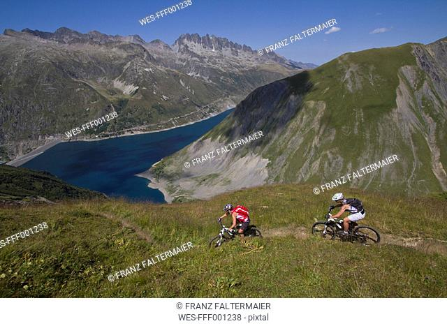 France, Dauphine, Vaujany, Bikers riding mountain bike on dirt track