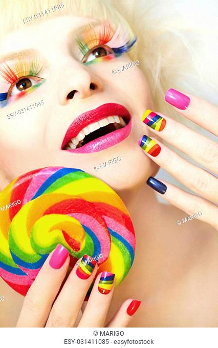 Rainbow manicure on artificial nails square shape, with a Lollipop in hand and colorful makeup