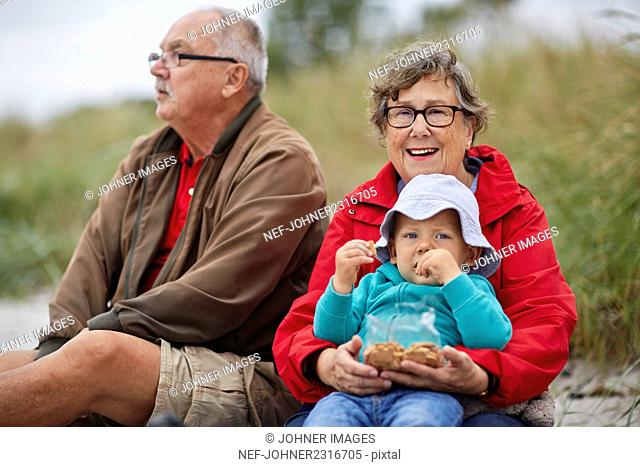 Grandparents with grandson sitting on beach