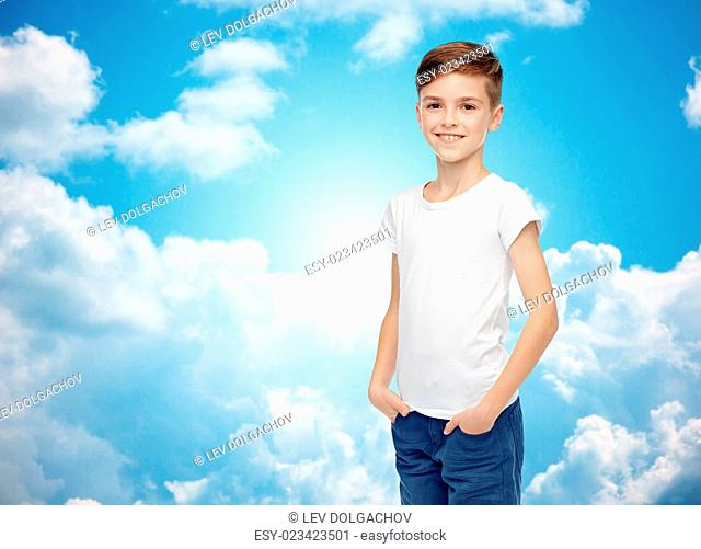 childhood, fashion, advertisement and people concept - happy boy in white t-shirt and jeans over blue sky and clouds background