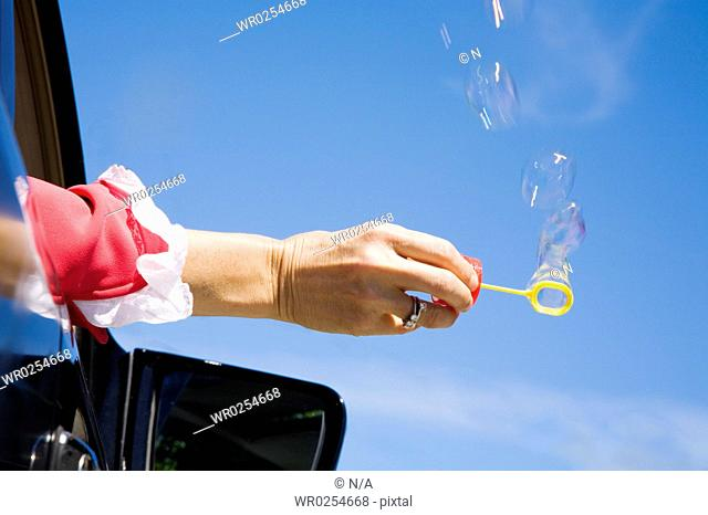 Woman blowing bubbles out car window