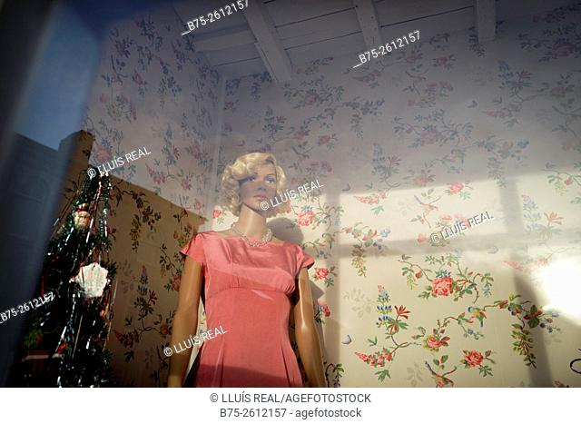 Feminine vintage fifties mannequin in a shop window with a christmas tree an vintage wall paper in the background. Grassington, North Yorkshire, Yorkshire Dales