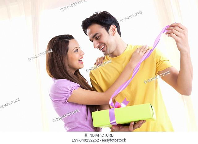 Young couple opening a gift