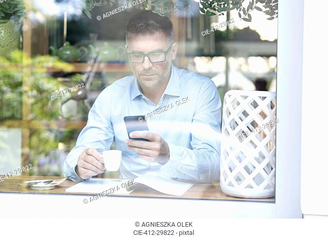 Businessman drinking espresso and checking cell phone at cafe window