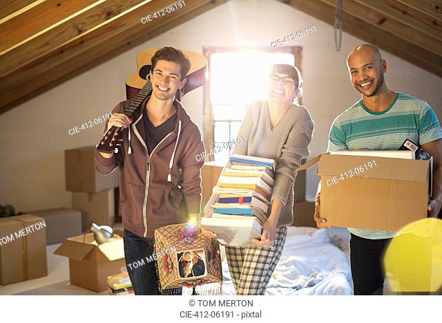 Friends unpacking boxes in attic