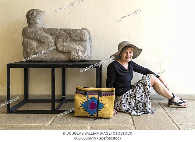 Woman, 67, sits beside a sculpture in the museum at the church and former convent of Santo Domingo, Oaxaca, Mexico
