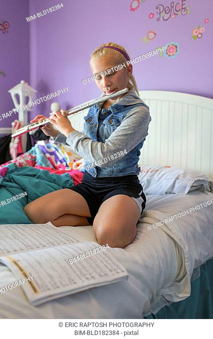 Caucasian girl practicing flute on bed