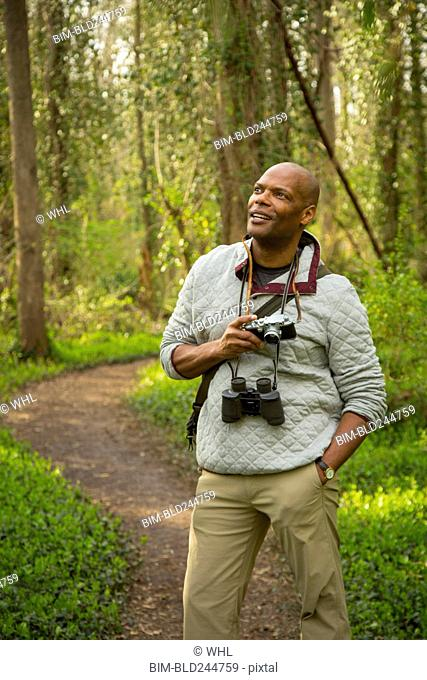 African American man standing on path in forest holding camera