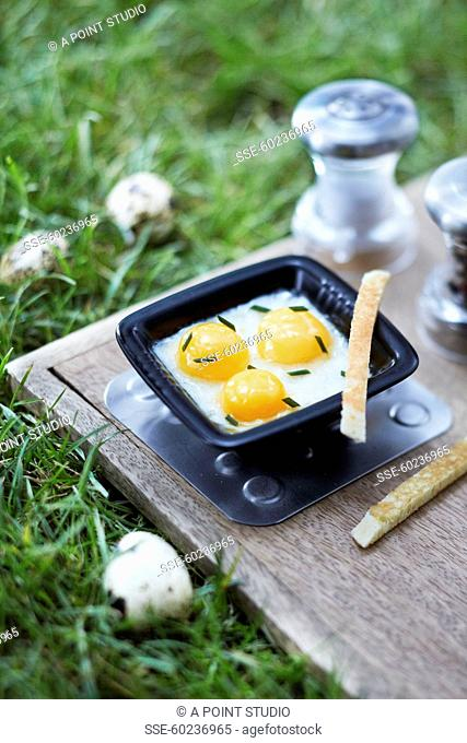 Coodled quail's eggs on a chopping board in the grass