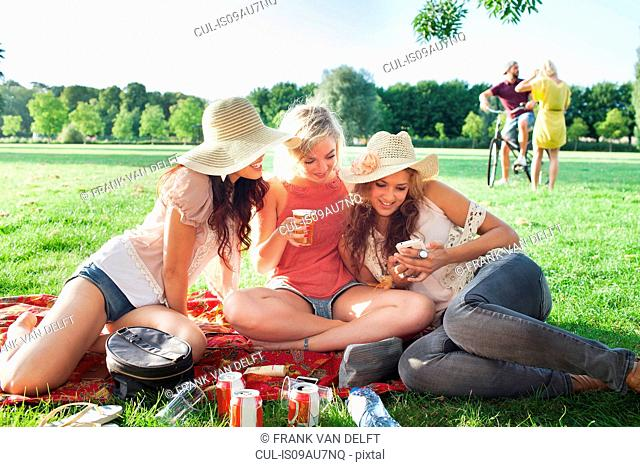 Female friends reading smartphone text at park party