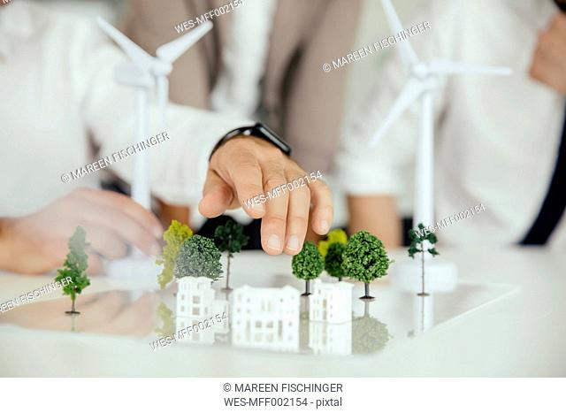 Close-up of business people wind turbine model and houses on conference table