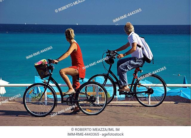 Couple riding past HI Hotel beach - promenade des anglais. Nice, Provence-Alpes-Cote d'Azur, France, Europe