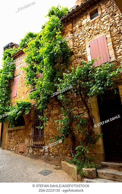 Overgrown exterior Facade in the medieval Village Roussillon, Provence, France