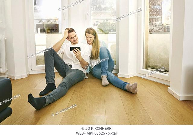 Smiling couple sitting on floor looking at cell phone