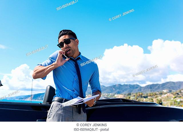 Anxious young businessman at coast parking lot talking on smartphone