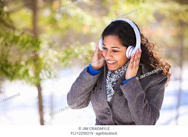 Young woman of South Asian ethnicity listening to music on Bluetooth headphones in Scanlon Creek Conservation Area; Ontario, Canada