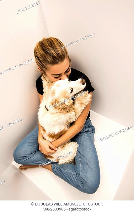 a 19 year old woman with her cocker spaniel in a white box