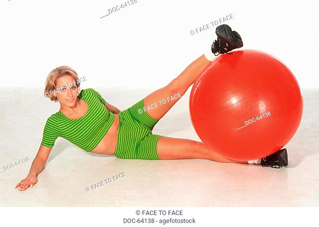 Young adult woman does doing sports practices - a red seat ball in the leg scissors hold