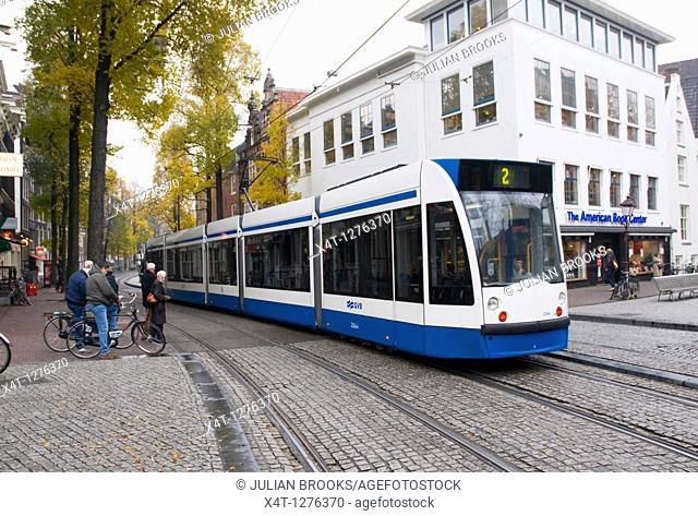 A tram travelling past the American Bookshop in Amsterdam while people wait on bicycles to cross the street