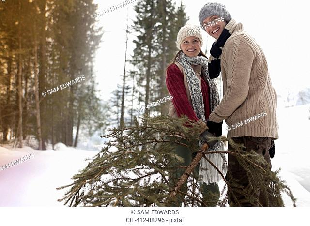 Portrait of happy couple with fresh Christmas tree in snowy woods