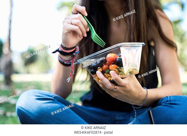 Young woman sitting in a park, eating salad