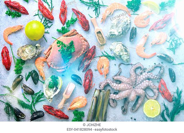 Seafood background - fresh mussels, molluscs, oysters, octopus, razor shells, shrimps, crab, crawfish, crayfish, seaweed, lemon, spices