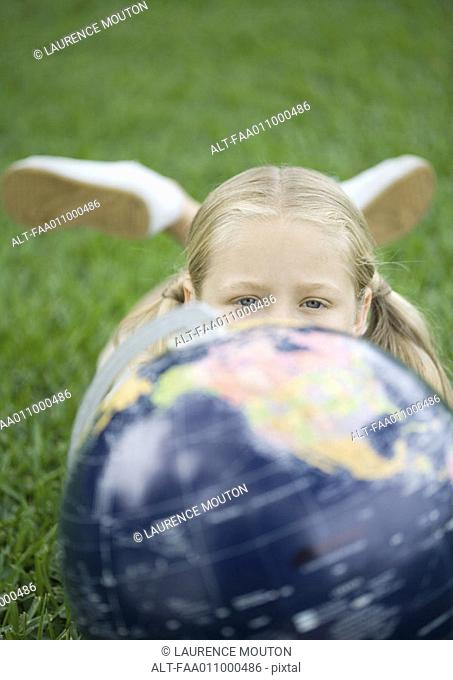Girl lying on grass with globe, looking at camera