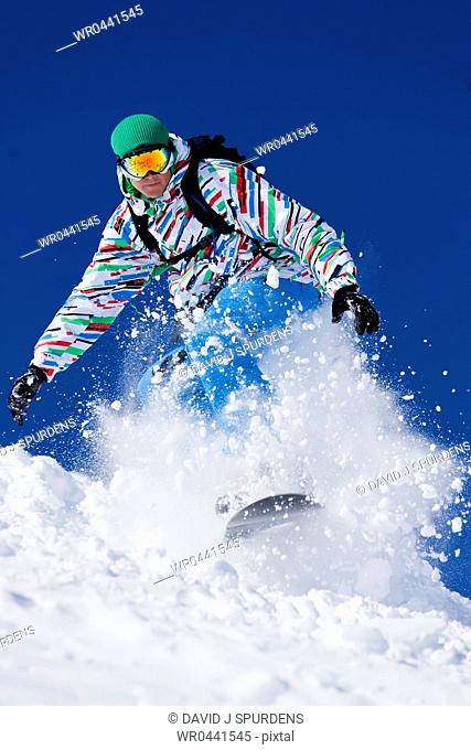 A Snowboarder riding fast