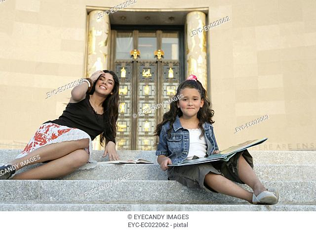 woman and child outside sitting on steps in the sun with educational book