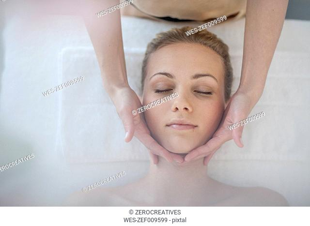 Young woman lying on massage table receiving beauty treatment
