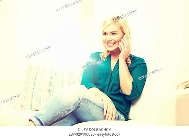 people, technology, communication and leisure concept - happy young woman calling on smartphone at home