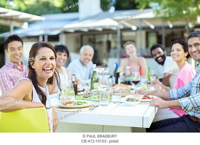 Friends smiling at table outdoors