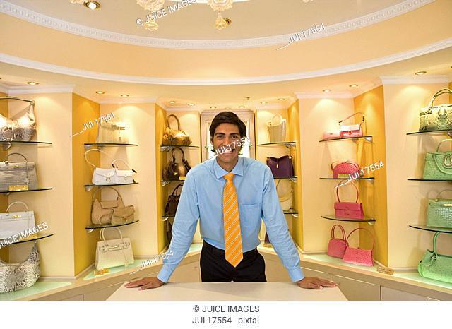 Salesman posing in front of purses