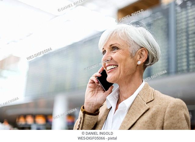 Smiling senior businesswoman on cell phone at the airport