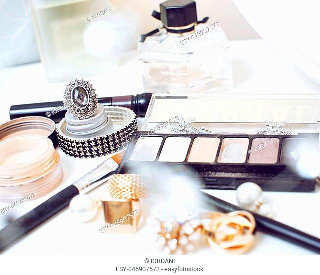 Jewelry table with lot of girl stuff on it, little mess in cosmetic brushes, women interior concept, perfume elegance things, little princess makeup