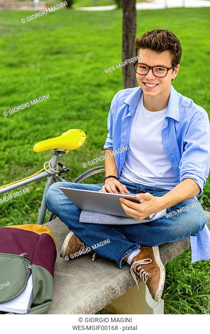 Portrait of smiling young man sitting on a bench using laptop