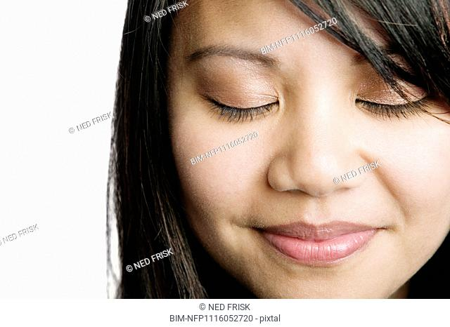 Asian woman smiling with eyes closed