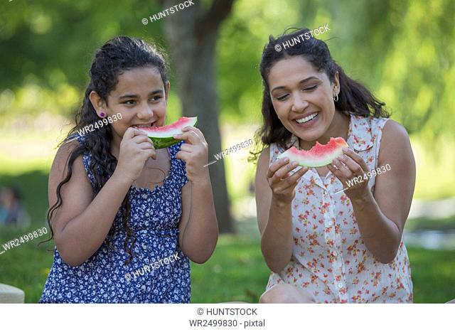 Happy Hispanic mother with her teen daughter eating watermelon in park