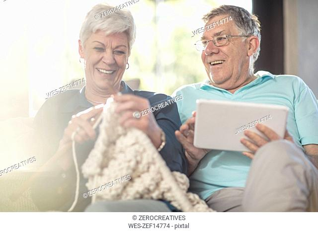 Happy senior couple on couch at home knitting and using tablet