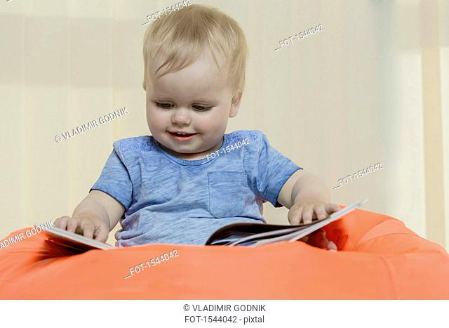 Close-up of cute smiling girl reading book while sitting on bean bag at home