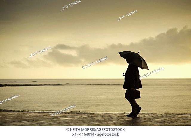 A man sheltering under an umbrella on a wet summer evening, Aberystwyth Wales UK