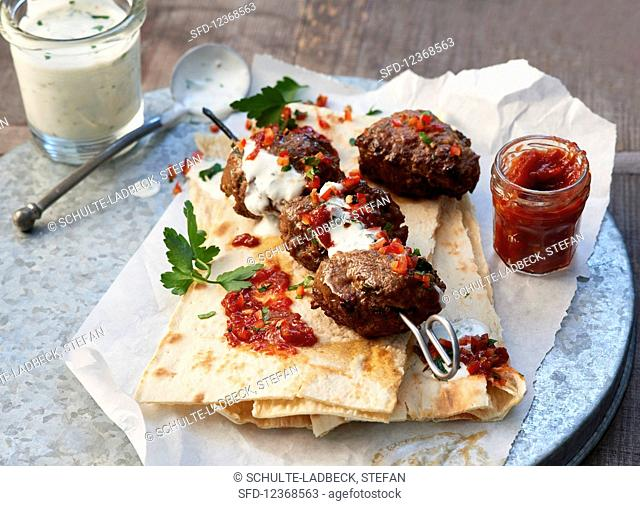 Meatballs on thin flatbread with a garlic dip and a hot pepper dip