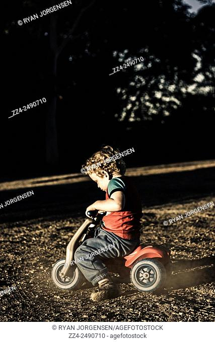 Side on portrait of a young three year-old child riding on toy bicycle at dirt road location. Childhood playtime activities