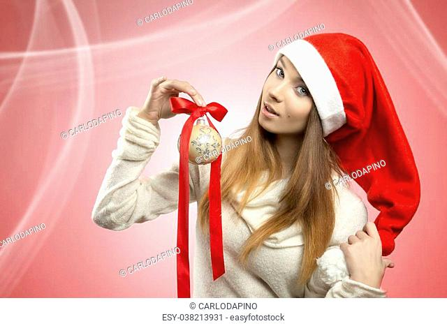 very pretty christmas female with long smooth hair and santa claus hat taking in the hand elegant bauble and wearing winter sweater