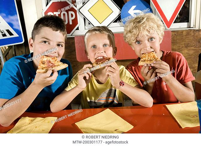Three boys eating pizza at driver training area