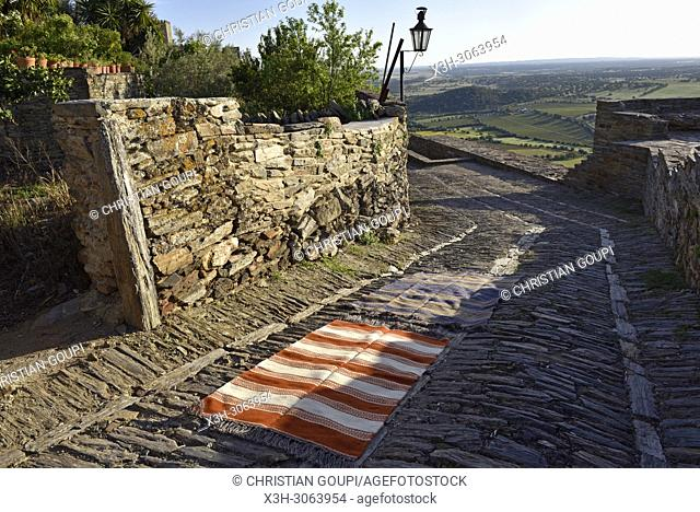 some types of blankets and carpets from the Fabrica Alentejana de Lanificios, displayed on a cobbled street in the perched village Monsaraz