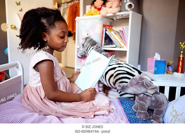 Cute girl sitting on her bed reading storybook