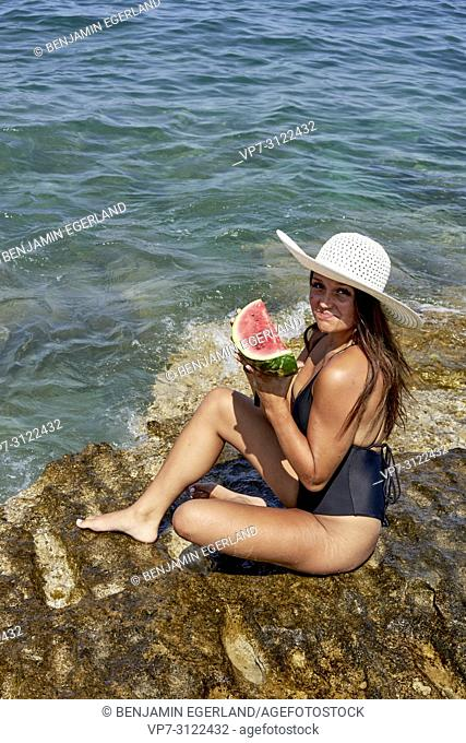 woman with water melon and sunhat sitting on rock in sea, Chersonissos, Crete, Greece