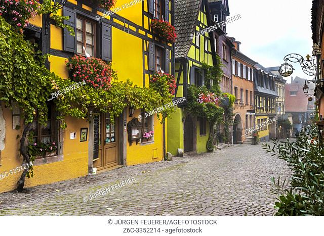 colorful houses in the village Riquewihr, Alsace Wine Route, France, vine and flower-bedecked half-timbered houses