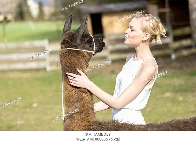 Woman face to face with llama on a paddock
